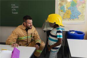 Firefighter talking to a school boy in a classroom