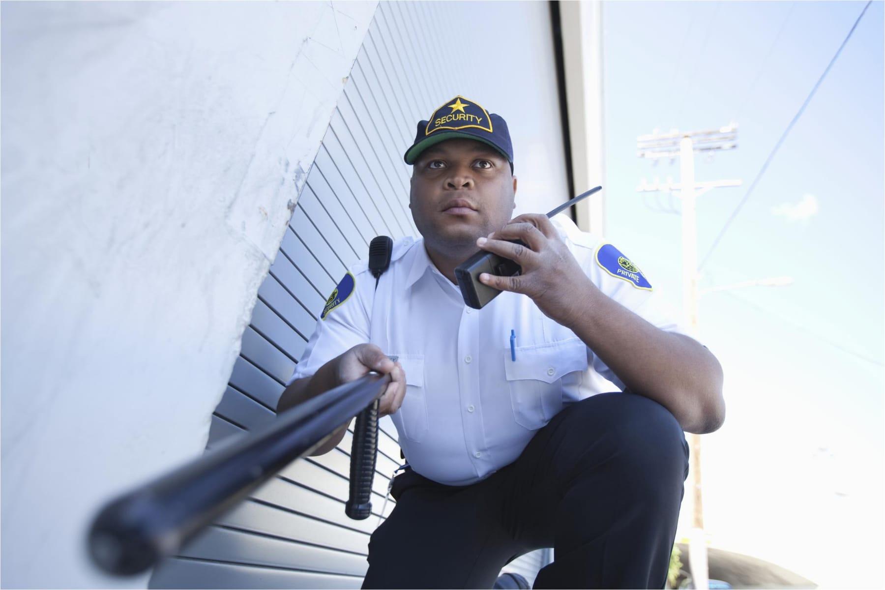 Security guard patrolling an area talking in a walkie talkie