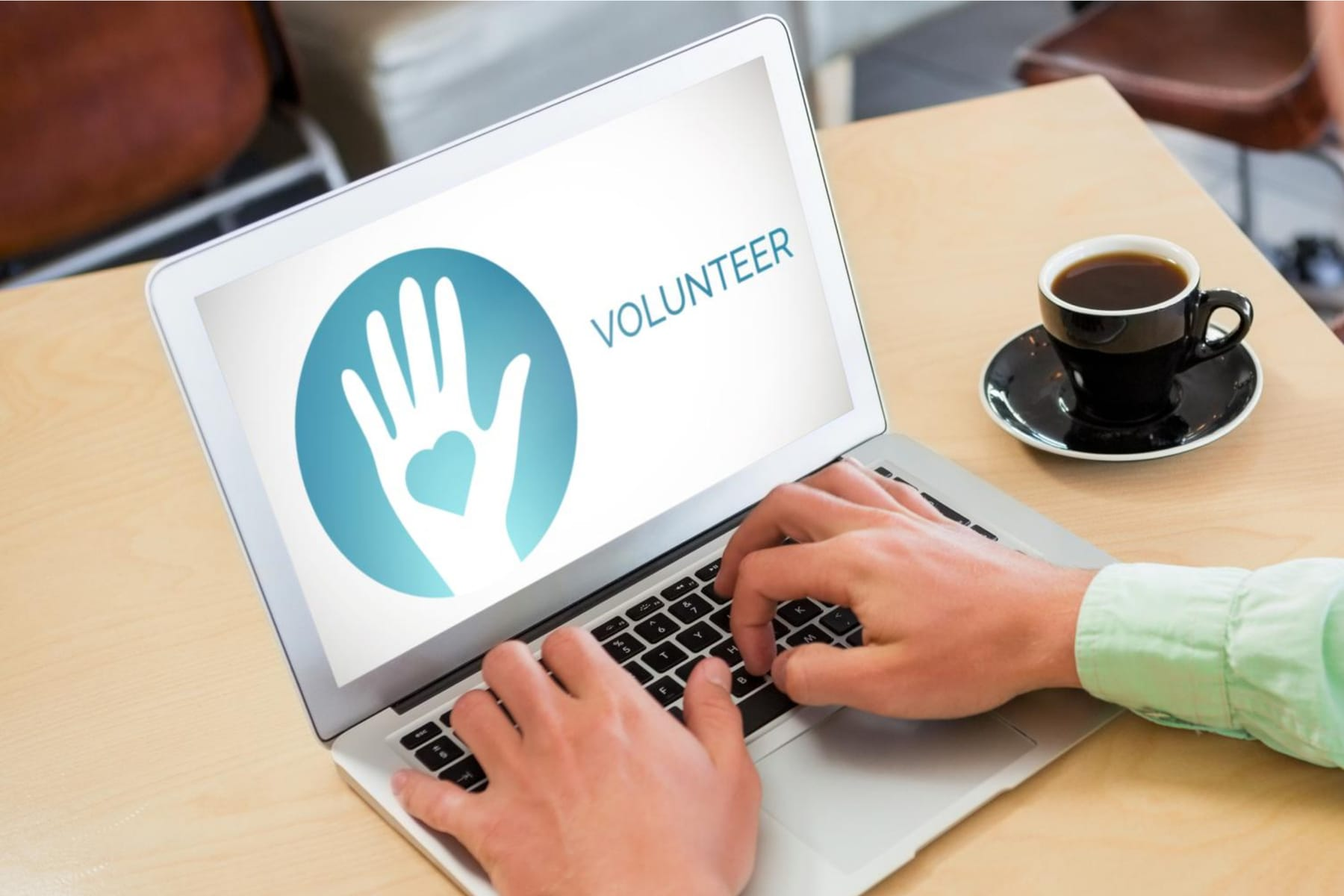 Man typing on his laptop with a volunteer icon on the screen