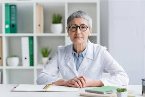Female doctor with grey hair sitting behind her desk wearing a laboratory coat