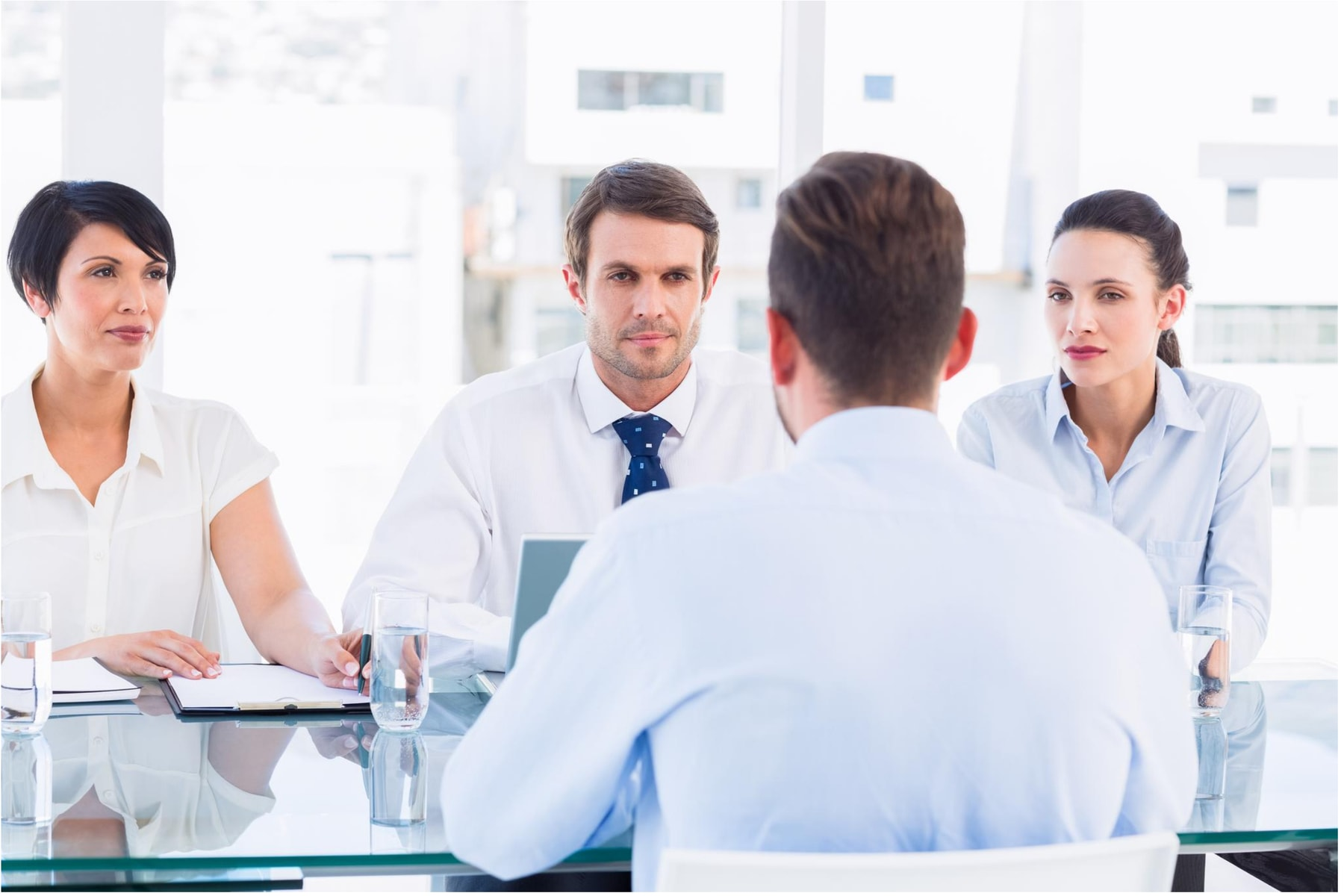 Three managers interviewing a male candidate during formal interview